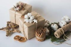 Bożenarodzeniowi prezentów pudełka z kwiatami, dekoracyjną przedmiota Eco bawełna, cynamon, świerczyn gałąź i jutowy linowy motek fotografia stock