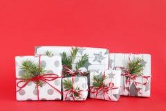 Bożenarodzeniowi prezentów pudełka zawijający szarość tapetują z białymi faborkami na czerwonym tle, dekorującym jedlinowe gałąź obraz royalty free