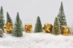 Bożenarodzeniowi prezenty w złocie pakuje blisko zabawek drzew Zdjęcia Royalty Free