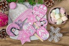 Bożenarodzeniowi przygotowania Miodownik, pingwiny, mitynki, kapelusze z asteryskami i kubek marshmallow na drewnianym tle, obrazy stock