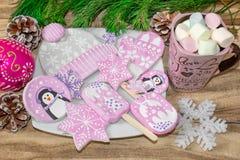 Bożenarodzeniowi przygotowania Miodownik, pingwiny, mitynki, kapelusze z asteryskami i kubek marshmallow na drewnianym tle, fotografia royalty free