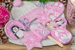 Bożenarodzeniowi przygotowania Miodownik, pingwiny, mitynki, kapelusze z asteryskami i kubek marshmallow na drewnianym tle, fotografia stock