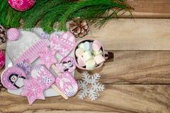 Bożenarodzeniowi przygotowania Miodownik, pingwiny, mitynki, kapelusze z asteryskami i kubek marshmallow na drewnianym tle, zdjęcia stock