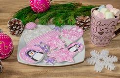 Bożenarodzeniowi przygotowania Miodownik, pingwiny, mitynki, kapelusze z asteryskami i kubek marshmallow na drewnianym tle, obraz stock