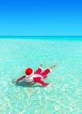 Bożenarodzeniowy Święty Mikołaj pływanie i relaksuje w oceanu turkusu wodzie Obrazy Stock