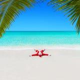 Bożenarodzeniowy Święty Mikołaj relaksuje na piasku przy ocean palmy plażą Obrazy Stock