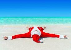 Bożenarodzeniowy Święty Mikołaj sunbathing przy tropikalną ocean plażą w wate Obrazy Royalty Free