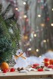 Bożenarodzeniowy anioł w drzewnych, czerwonych świeczkach na kolorowym tła bokeh wśród wystroju i Zdjęcie Royalty Free