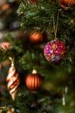 Bożenarodzeniowy balowy obwieszenie na sośnie rozgałęzia się z świątecznym tłem fotografia stock