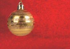 Bożenarodzeniowy bauble na czerwonej błyskotliwości zamazanym tle zdjęcia stock