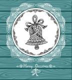 Bożenarodzeniowy Bell w okręgu w Doodle stylu z koronką na błękitnym drewnianym tle Fotografia Royalty Free