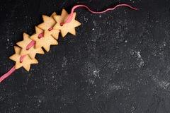 Bożenarodzeniowy czarny tło z ciastkami Zdjęcia Royalty Free