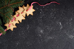 Bożenarodzeniowy czarny tło z ciastkami i jodła rozgałęziamy się Obraz Royalty Free
