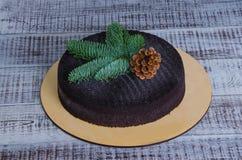 Bożenarodzeniowy czekoladowy aksamita tort dekorował z pinecone na drewnie fotografia royalty free