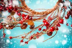 Bożenarodzeniowy czerwony jagoda wianek na błękitnym tle z śniegiem zdjęcia royalty free