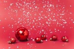 Bożenarodzeniowy czerwony tło z boże narodzenie piłkami i śnieg spada na one zdjęcie royalty free