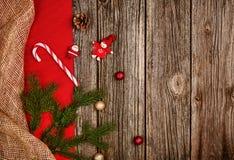 Bożenarodzeniowy dekoraci tło nad drewnianym stołem z czerwonym i bieliźnianym płótnem Obraz Stock