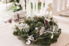 Bożenarodzeniowy dekoracyjny wianek holly, bluszcza, jemioły, cedru i leyland liścia sprigs z sosną, konusuje nad bielem zdjęcie royalty free