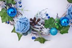 Bożenarodzeniowy dekoracyjny wianek z bluszczem opuszcza, jedlin piłki, rożki i sztuczni kwiaty, Zdjęcie Stock