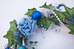 Bożenarodzeniowy dekoracyjny wianek z bluszczy liśćmi, jedlin piłkami i sztucznymi kwiatami, Obraz Stock