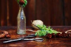 Bożenarodzeniowy drewniany tło Świerczyna rozgałęzia się i konusuje w rocznik butelce starych nożycach i podstępnym sznurze, Poję Obrazy Royalty Free