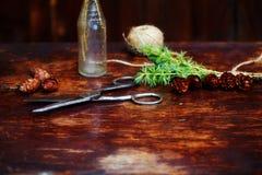Bożenarodzeniowy drewniany tło Świerczyna rozgałęzia się i konusuje w rocznik butelce starych nożycach i podstępnym sznurze, Poję Zdjęcia Royalty Free