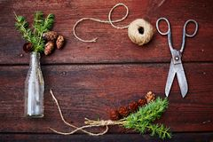 Bożenarodzeniowy drewniany tło Świerczyna rozgałęzia się i konusuje w rocznik butelce starych nożycach i podstępnym sznurze, Poję Fotografia Stock