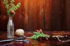 Bożenarodzeniowy drewniany tło Świerczyna rozgałęzia się i konusuje w rocznik butelce starych nożycach i podstępnym sznurze, Poję Fotografia Royalty Free