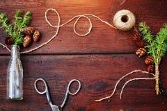 Bożenarodzeniowy drewniany tło Świerczyna rozgałęzia się i konusuje w rocznik butelce starych nożycach i podstępnym sznurze, Poję Zdjęcia Stock