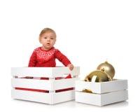 Bożenarodzeniowy dziecka dziecko w Santa kapeluszowego chwyta złocistej balowej dekoraci Zdjęcia Royalty Free