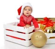 Bożenarodzeniowy dziecka dziecko w Santa kapeluszowego chwyta złocistej balowej dekoraci blisko Obrazy Stock