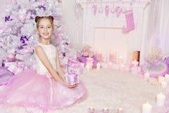 Bożenarodzeniowy dziecko dziewczyny otwarcia teraźniejszości prezenta pudełka przód Xmas drzewo fotografia stock