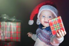 Bożenarodzeniowy dziecko jest ubranym Święty Mikołaj kapelusz trzyma teraźniejszość Obrazy Royalty Free
