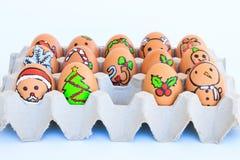 Bożenarodzeniowy jajko z twarzami rysować układał w kartonie Zdjęcia Royalty Free