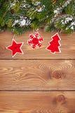 Bożenarodzeniowy jedlinowy drzewo z śnieżnym i wakacyjnym wystrojem na nieociosany drewnianym Fotografia Stock