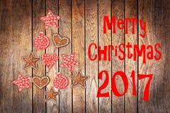 Bożenarodzeniowy kartka z pozdrowieniami 2017, wieśniaków ornamenty na drewnie zaszaluje tło Obrazy Stock