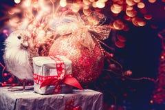 Bożenarodzeniowy kartka z pozdrowieniami z prezentów pudełkami, dekoraci piłką i ptakiem przy świątecznym bokeh oświetleniem, Zdjęcia Royalty Free