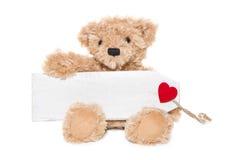 Bożenarodzeniowy miś trzyma wiadomość z czerwonym sercem odizolowywającym dalej Zdjęcie Stock