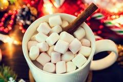 Bożenarodzeniowy nastrój - biały kubek kakao z marshmallows i cynamonowym kijem w górę, choinki gałąź z girlandą obraz stock