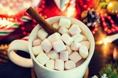 Bożenarodzeniowy nastrój - biały kubek kakao z marshmallows i cynamonowym kijem w górę, choinki gałąź z girlandą fotografia stock