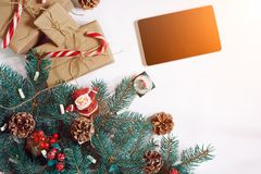Bożenarodzeniowy online zakupy tło Pastylka ekran z kopii przestrzenią, świerkowe gałąź, prezenty na białym tle słońce Fotografia Stock