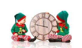 Bożenarodzeniowy pojęcie Dwa elfa mały pomagier Santa z zegaru iso Obraz Royalty Free