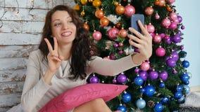 Bożenarodzeniowy pojęcie - młoda kobieta bierze selfie fotografię blisko dekorował choinki Kędzierzawa brunetka robi zwycięstwu zbiory wideo