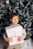 Bożenarodzeniowy portret młodej chłopiec wygodna atmosfera wokoło choinki Śliczny berbeć trzyma białego prezenta pudełko Zdjęcia Royalty Free