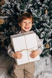 Bożenarodzeniowy portret młodej chłopiec wygodna atmosfera wokoło choinki Śliczny berbeć trzyma białego prezenta pudełko Zdjęcie Stock