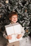 Bożenarodzeniowy portret młodej chłopiec wygodna atmosfera wokoło choinki Śliczny berbeć trzyma białego prezenta pudełko Zdjęcie Royalty Free