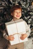 Bożenarodzeniowy portret młodej chłopiec wygodna atmosfera wokoło choinki Śliczny berbeć trzyma białego prezenta pudełko Obrazy Stock