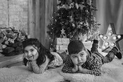 Bożenarodzeniowy portret piękni uśmiechnięci małe dzieci kłama na podłoga z teraźniejszość pod choinką Zima wakacje Xmas fotografia royalty free
