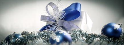 Bożenarodzeniowy prezent i błękitne Bożenarodzeniowe piłki na świątecznym bielu plecy Zdjęcie Stock