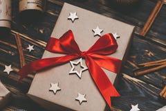 Bożenarodzeniowy prezent lub teraźniejszości pudełko zawijający w Kraft papierze z dekoracją na nieociosanym tle od above mieszka Fotografia Stock